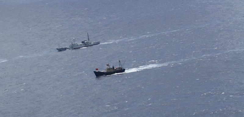 In this photo provided by Japan Coast Guard, a Japan Coast Guard patrol boat, back, sails alongside a Hong Kong fishing boat, foreground, in the water, 52 kilometers (32 miles) west of the Uotsuri Island, one of the islands of Senkaku in Japanese and Diaoyu in Chinese, in East China Sea, Wednesday, Aug. 15, 2012. Hong Kong activists trying to reach the disputed islands claimed by Japan, China and Taiwan said Wednesday that they were being tailed by Japanese government ships trying to stop them, as territorial disputes continue to raise tensions among Asian powerhouses. (AP Photo/Japan Coast Guard) EDITORIAL USE ONLY