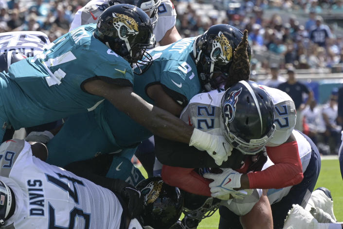 Tennessee Titans running back Derrick Henry (22) dives past Jacksonville Jaguars outside linebacker Myles Jack, left, and defensive end Dawuane Smoot (91) for a 1-yard touchdown run during the first half of an NFL football game, Sunday, Oct. 10, 2021, in Jacksonville, Fla. (AP Photo/Phelan M. Ebenhack)