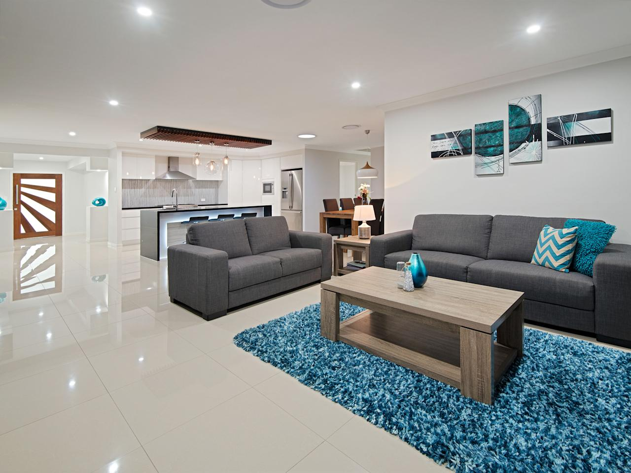 <p>Polished marble floors and soft spot lighting highlight the luxurious finishing to the open plan living room, with the sleek and ultra-modern kitchen area in the background. </p>