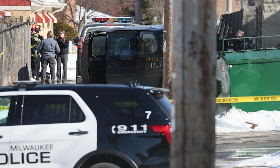 Police investigate three bodies found in a garage in the 4700 block of West Burleigh Street in Milwaukee. Here they work in an alley near dumpsters behind a building.