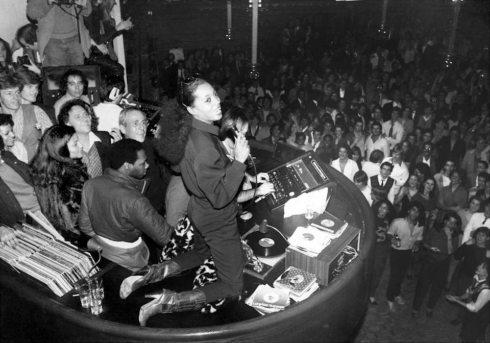 <p>Singer Diana Ross takes over the microphone while kneeling on the DJ booth at the famed Studio 54. </p>