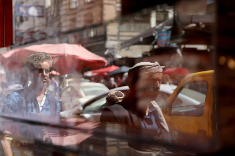 People are reflected on a shop door as they walk on a street in Sanaa, Yemen