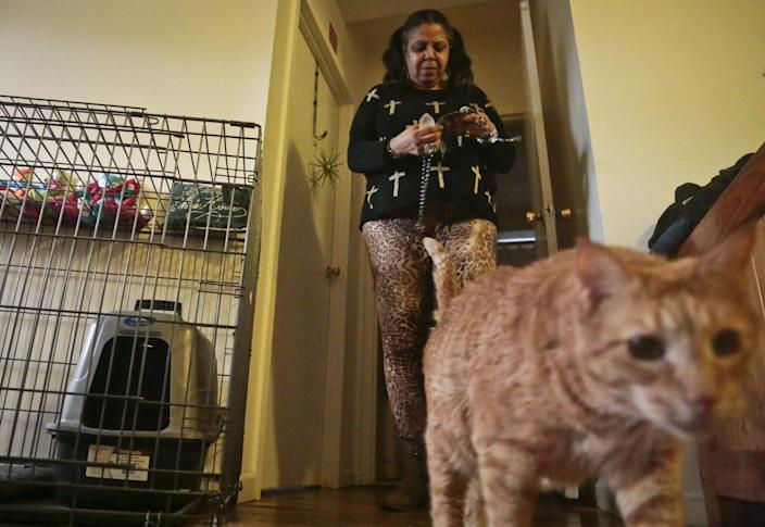 Pamela Isaac and one of her three cats, Lucy, inside their apartment at a shelter for victims of domestic violence, Tuesday March 18, 2014 in New York. The shelter is the city's first pet-friendly domestic violence shelter, one in a fast-growing number of similar sanctuaries around the country that reflect growing awareness that animals can be both victims of family violence and key factors in their owners' willingness to flee. (AP Photo/Bebeto Matthews)