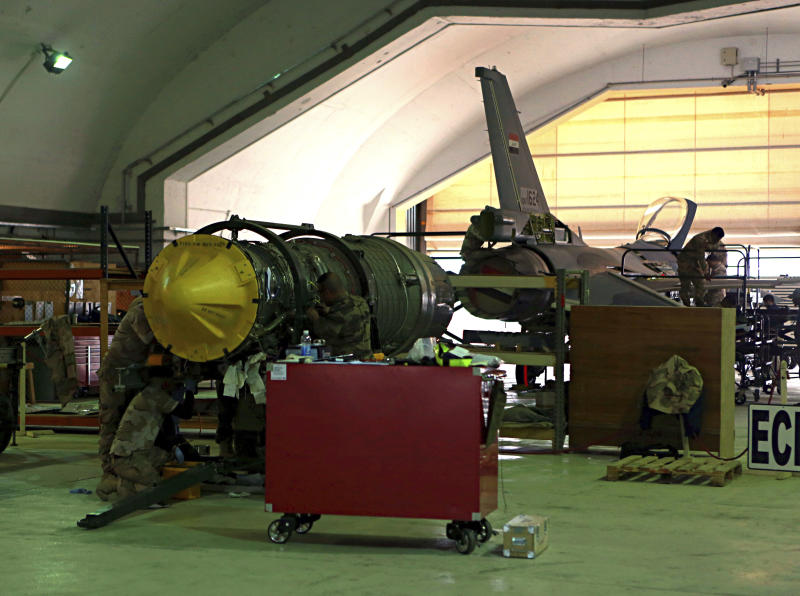 FILE - in this Tuesday, Feb. 13, 2018 file photo, U.S. and Iraqi engineers do engine maintenance of a U.S.- made Iraqi Air Force F-16 fighter jet at the Balad, Iraq. Militants fired early Saturday, June 15, 2019 three mortar shells on an air base just north of Baghdad where American trainers are present, causing a small fires but no casualties, the Iraqi military said. (AP Photo/Khalid Mohammed, File)