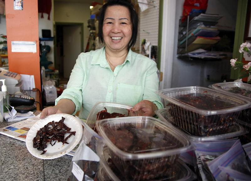 This March 13, 2014 photo shows Kimheng Chou showing off her homemade beef jerky at the Dessert Shop and Bakery in Lowell, Mass. Lowell now is home to one of the largest populations of Cambodians outside Cambodia. (AP Photo/Elise Amendola)