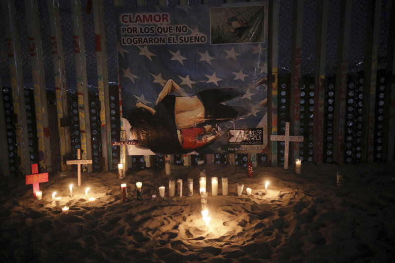 Candles are placed next to the border fence that separates Mexico from the United States, in memory of migrants who have died during their journey toward the U.S., in Tijuana, Mexico, late Saturday, June 29, 2019. On the border fence hangs a cartoon depiction of a news photograph of the bodies of Salvadoran migrant Óscar Alberto Martínez Ramírez and his daughter Valeria, who drowned on Sunday, June 23 on the banks of the Rio Grande between Matamoros, Mexico, and Brownsville, Texas. (AP Photo/Emilio Espejel)