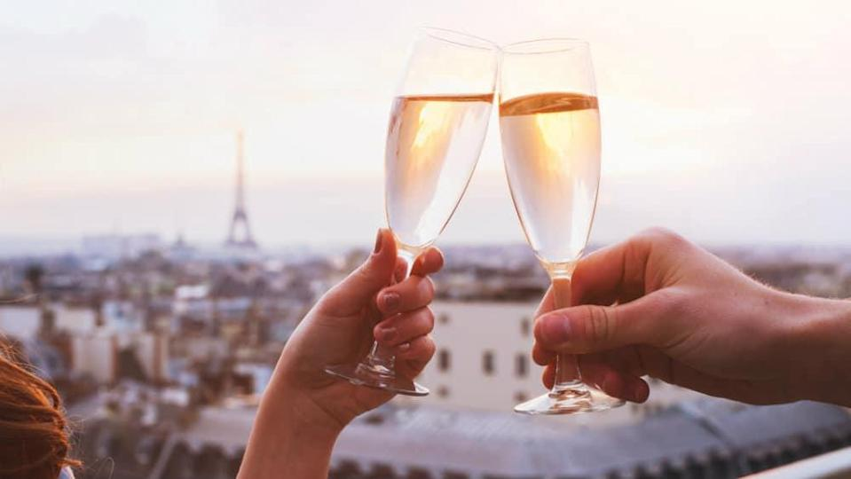 Two hands holding champagne glasses toasting each other with Paris in the background