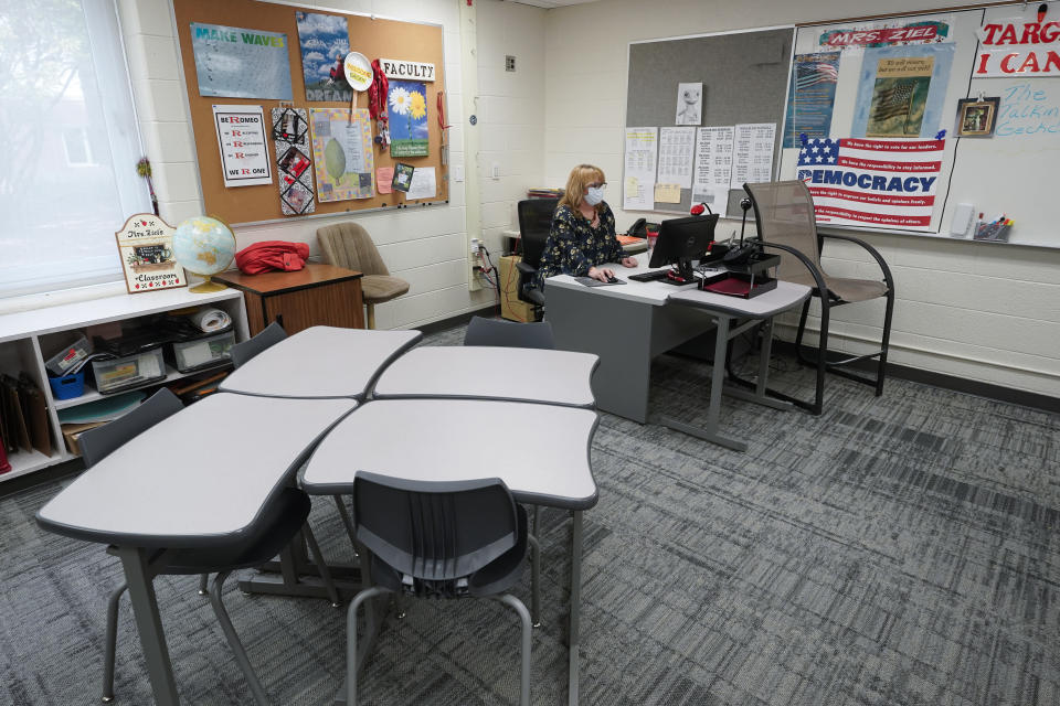 """Sue Ziel, a sixth grade social studies teacher at Romeo Middle School, works in her classroom in Romeo, Mich., Tuesday, April 27, 2021. """"I remember sitting in tears and telling my husband 'I don't know if I can do this,' and those words have never come out of my mouth,"""" she said as the pandemic hit. Ziel left a job in advertising 24 years ago to teach. Even before then, she said the demands of the job had increased. (AP Photo/Paul Sancya)"""