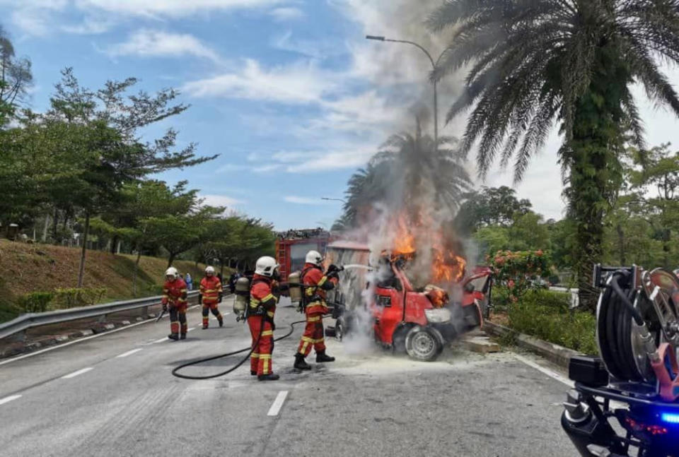 Firemen douse flames from the burning courier lorry where the driver was trapped after a crash along Jalan Tasek Utara in Johor Baru, September 28, 2021. — Picture courtesy of the Johor Fire and Rescue Department
