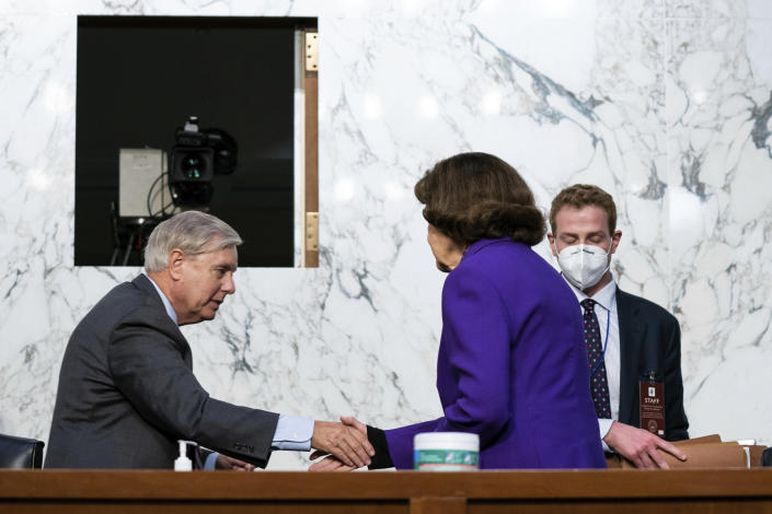 Sen. Lindsey Graham, R-S.C., shakes hands with Sen. Dianne Feinstein, D-Calif., following the fourth day of a confirmation hearing for Supreme Court nominee Amy Coney Barrett, before the Senate Judiciary Committee, Thursday, Oct. 15, 2020, on Capitol Hill in Washington. (Anna Moneymaker/The New York Times via AP, Pool)