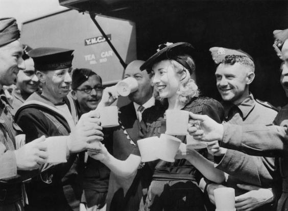 Dame Vera Lynn serves cups of tea to servicemen in 1942 (Getty)