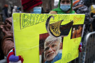 Protesters hold signs on police barricades outside the Consulate General of India, Tuesday, Jan. 26, 2021, in the Manhattan borough of New York. Tens of thousands of protesting farmers have marched, rode horses and drove long lines of tractors into India's capital, breaking through police barricades to storm the historic Red Fort. The farmers have been demanding the withdrawal of new laws that they say will favor large corporate farms and devastate the earnings of smaller scale farmers. Republic Day marks the anniversary of the adoption of India's constitution on Jan. 26, 1950. (AP Photo/John Minchillo)