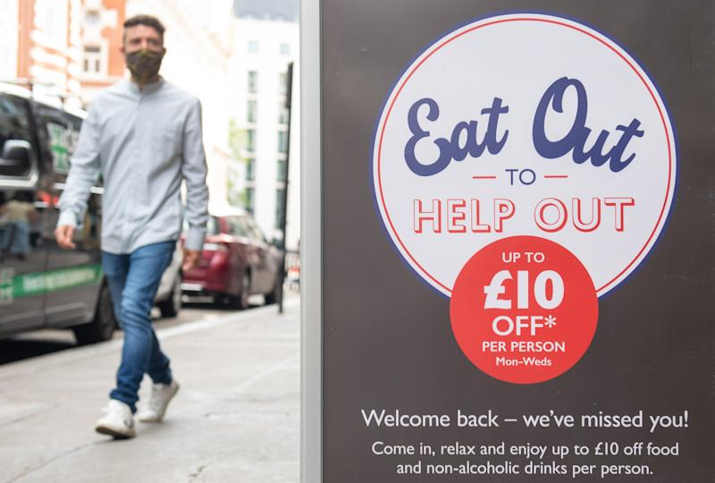 File photo dated 3/8/2020 of a man passing a sign advertising the 'Eat Out to Help Out' scheme, in Covent Garden, London. More than 35 million half-price meals have been served by restaurants across the UK in the first two weeks of the Government's Eat Out to Help Out scheme.