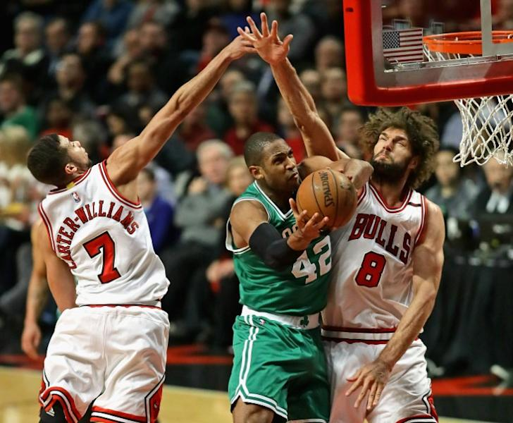 Al Horford of the Boston Celtics puts up a shot between Michael Carter-Williams (L) and Robin Lopez of the Chicago Bulls during Game Three of the Eastern Conference Quarterfinals