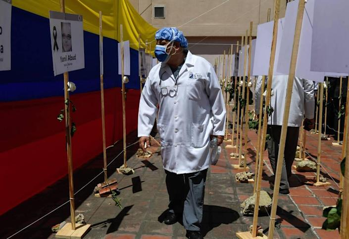 A healthcare worker walks past photos of doctors who died from COVID-19 at the Venezuelan Medical Federation in Caracas last year.