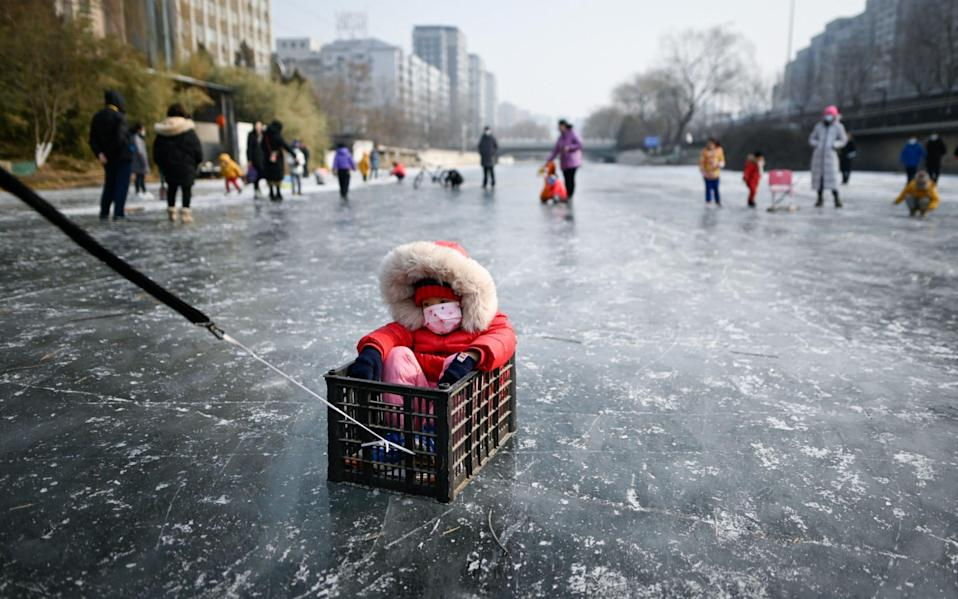 A man pulls a child sitting in a box on a frozen river in Beijing - WANG ZHAO/AFP