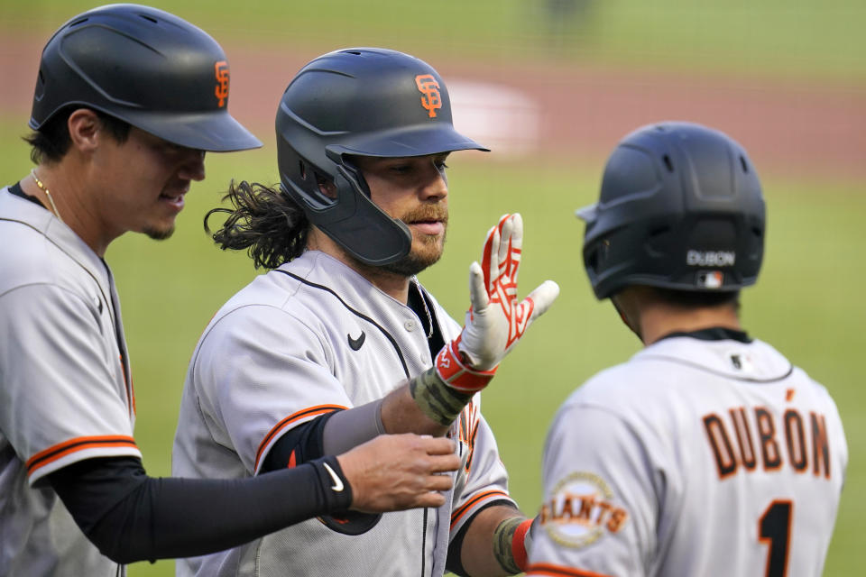 San Francisco Giants' Brandon Crawford, center, is greeted by Wilmer Flores, left, and Mauricio Dubon (1) as he crosses home plate after hitting a two-run home run off Pittsburgh Pirates starting pitcher Tyler Anderson during the first inning of a baseball game in Pittsburgh, Saturday, May 15, 2021. (AP Photo/Gene J. Puskar)