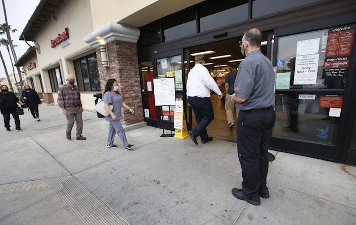 "People who work at grocery stores can't work from home. Here, Anthony Capone, a Vons supervisor in Torrance, greets customers in April. <span class=""copyright"">(Al Seib / Los Angeles Times)</span>"