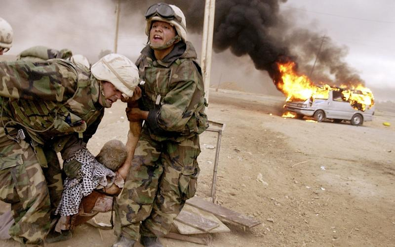 US soldiers drag a wounded civilian from a burning car in Iraq, April 2003 - Cheryl Diaz Meyer/AP