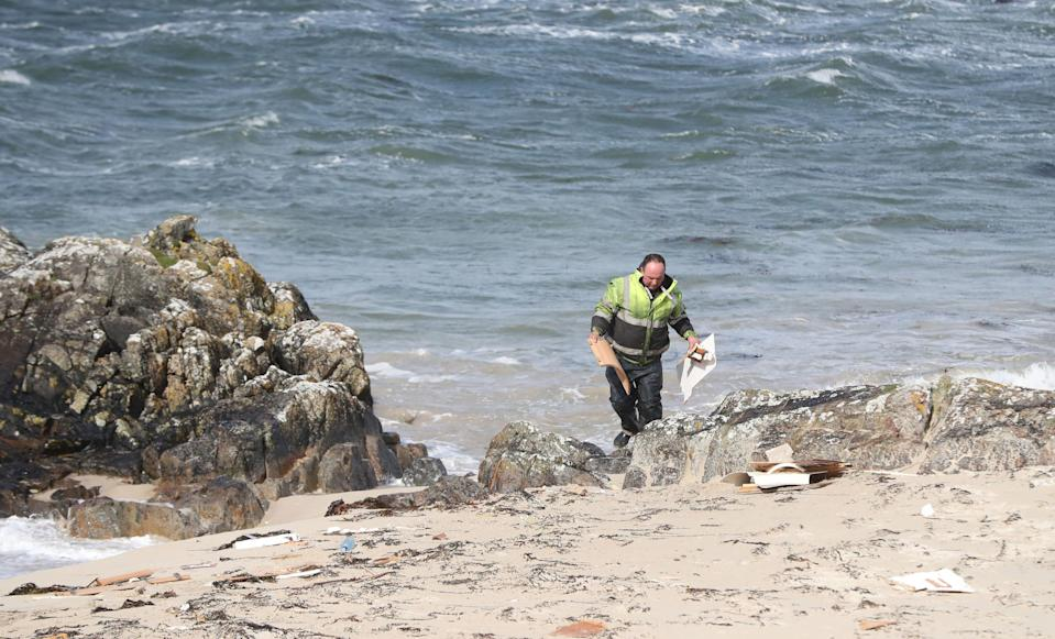 A man picks up debris at the scene. (Photo by Niall Carson/PA Images via Getty Images)