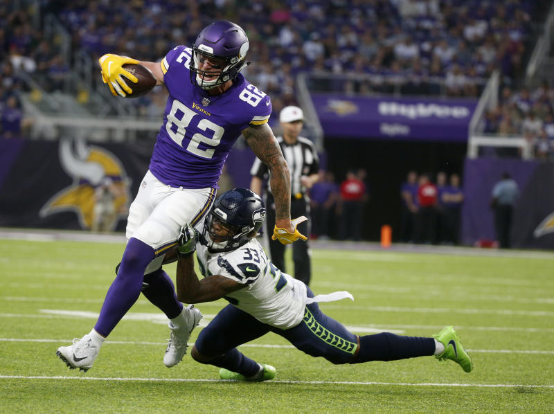 FILE - In this Friday, Aug. 24, 2018 file photo, Minnesota Vikings tight end Kyle Rudolph (82) runs from Seattle Seahawks defensive back Tedric Thompson after making a reception during the first half of an NFL preseason football game in Minneapolis. Just because the Minnesota Vikings drafted a tight end, Irv Smith Jr., in the second round doesn't mean they're going to cut or trade veteran Kyle Rudolph. There's room for both of them in the offense, as long as the Vikings can make space under the salary cap. (AP Photo/Bruce Kluckhohn, File)