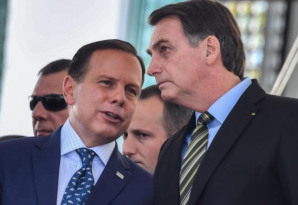 Brazilian President Jair Bolsonaro (R) listens to Sao Paulo's Governor Joao Doria while attending a military event in Sao Paulo, Brazil, on October 11, 2019. (Photo by NELSON ALMEIDA / AFP) (Photo by NELSON ALMEIDA/AFP via Getty Images)