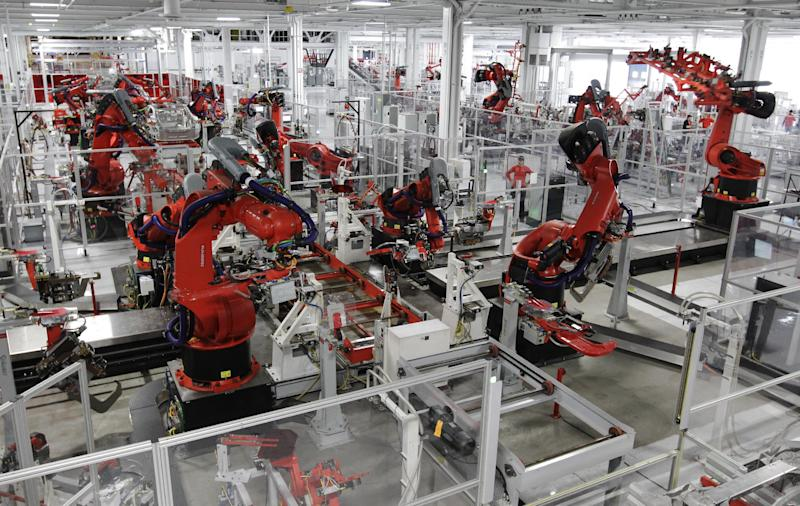 FILE- In this Friday, June 22, 2012, file photo, robots assemble a Tesla Model S at the Tesla factory in Fremont, Calif. U.S. industrial production rose in June as factories made more cars, machines and business equipment. Factory output recovered to levels reached earlier this spring but appears to be leveling off. The Federal Reserve says factory output rose 0.7 percent last month, after falling by the same amount in May. (AP Photo/Paul Sakuma, File)