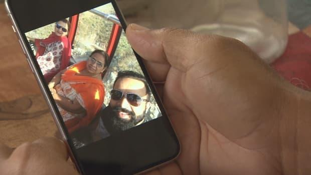 Neeraj Walia holds his phone, which displays a photograph of him and his mother. Walia says she is isolating in her room in northern India to try to stay safe from the coronavirus, which has infected several members of their family. (CBC News - image credit)