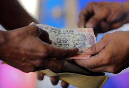 A customer hands a 50-Indian rupee note to an attendant at a fuel station in Ahmedabad