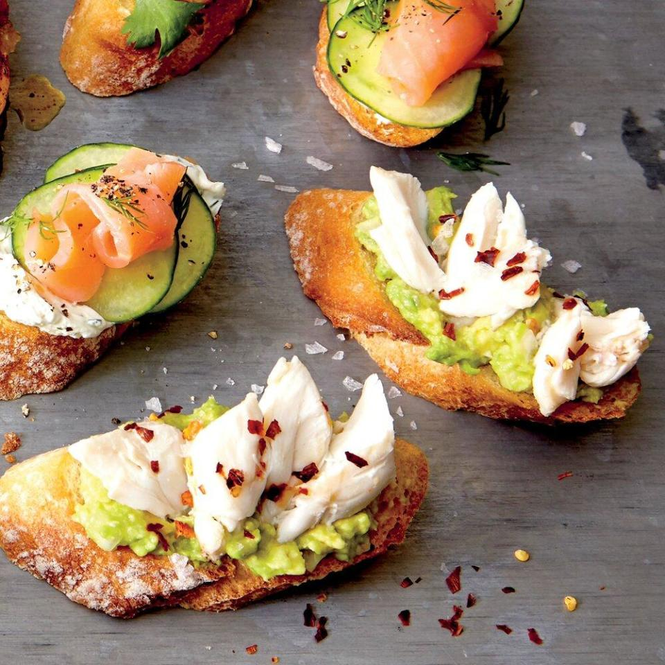 """<p>Top baked bread slices with mashed avocado and crab to make this tasty appetizer. </p> <p><a href=""""https://www.myrecipes.com/recipe/crostini-avocado-crab-flake-salt"""" rel=""""nofollow noopener"""" target=""""_blank"""" data-ylk=""""slk:Crostini with Avocado, Crab, and Flake Salt Recipe"""" class=""""link rapid-noclick-resp"""">Crostini with Avocado, Crab, and Flake Salt Recipe</a></p>"""