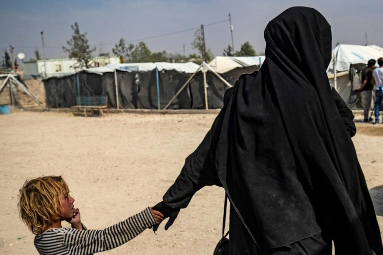 A French woman held at Al-Hol camp holds a child by the hand (AFP Photo/Delil SOULEIMAN)