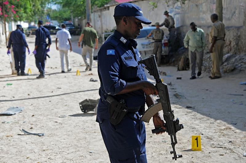 Security forces personnel investigate the scene of a car bomb which killed Somali journalist Hindiyo Haji Mohamed in the Hodan neighborhood of Mogadishu on December 3, 2015