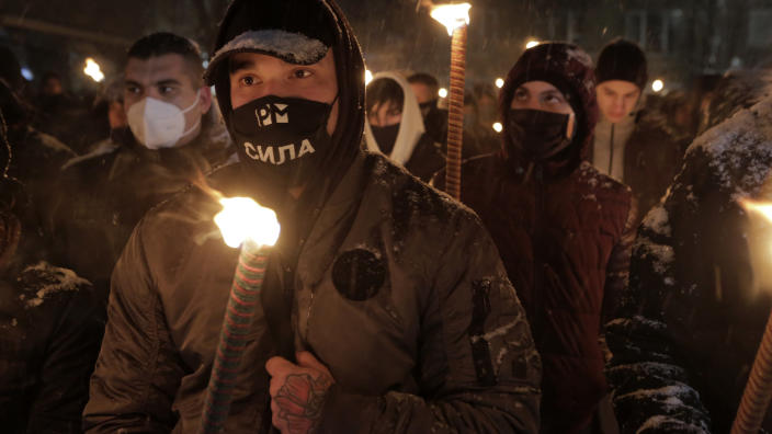 Bulgarian far-right nationalists hold torches as they gather in the country's capital, to honour a World War II general known for his anti-Semitic and pro-Nazi activities, in Sofia, Saturday, Feb. 13, 2021. Braving sub-zero temperatures, hundreds of dark-clad supporters of the Bulgarian National Union group flocked to a central square where they had planned to kick off the annual Lukov March, a torch-lit procession held every February to the former house of Gen. Hristo Lukov. (AP Photo/Valentina Petrova)