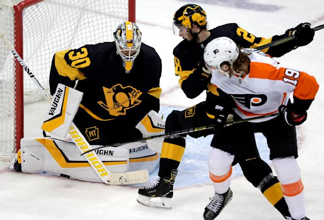 Pittsburgh Penguins goaltender Matt Murray (30) stops a shot by Philadelphia Flyers' Nolan Patrick (19) with Marcus Pettersson defending during the first period of an NHL hockey game in Pittsburgh, Sunday, March 17, 2019. (AP Photo/Gene J. Puskar)