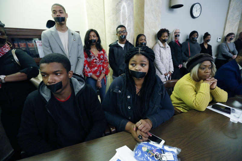 Prison reform advocates, wore a strip of tape across their mouths as a silent protest during a joint hearing of the House Corrections and Judiciary B Committees to address current corrections issues, Thursday, Feb. 13, 2020 at the Capitol in Jackson, Miss. Lawmakers heard from the head of the state parole board and a justice think tank on current corrections issues. (AP Photo/Rogelio V. Solis)