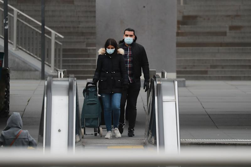 "A couple wearing a protective facemask walks at La Defense, near Paris, on March 16, 2020, while protective measures are taken in France against the spread of the COVID-19. - France has closed down all schools, theatres, cinemas and shops not selling ""non-essential"" items such as food in an effort to stop the spread of the virus. (Photo by Ludovic Marin / AFP) (Photo by LUDOVIC MARIN/AFP via Getty Images)"
