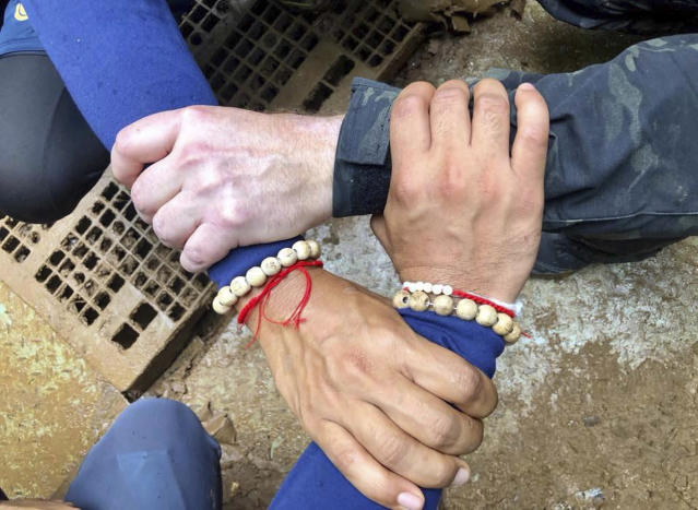 "<p>This photo on the Thailand navy SEAL Facebook page on July 8, 2018, shows rescuers' hands locked with a caption reading ""We Thai and the international teams join forces to bring the young Wild Boars home."" The 12 boys on the Young Boars team and their coach had been trapped since June 23 in a cave in Chiang Rai province, northern Thailand. (Photo: Thailand navy SEAL Facebook page via AP) </p>"