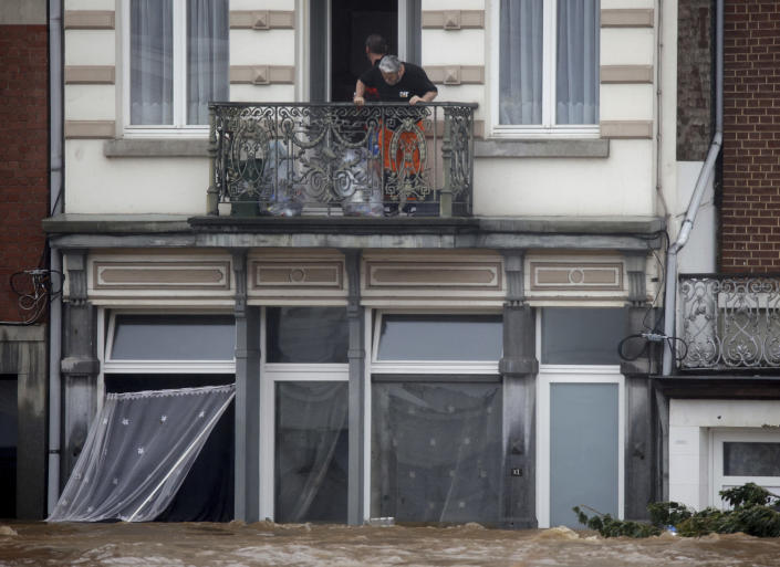 Rescue workers look down from a balcony as floodwaters run down a main street in Pepinster, Belgium, Thursday, July 15, 2021. Heavy rainfall is causing flooding in several provinces in Belgium with rain expected to last until Friday. (AP Photo/Olivier Matthys)