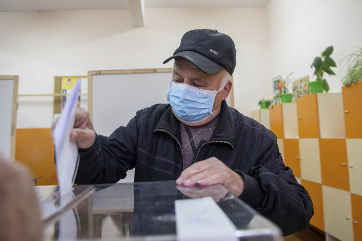 A man casts his ballot during parliamentary elections in the town of Bankya near capital Sofia, Bulgaria on Sunday, April 4, 2021. Bulgarians are heading to the polls on Sunday to cast ballots for a new parliament after months of anti-government protests and amid a surge of coronavirus infections. (AP Photo/Visar Kryeziu)