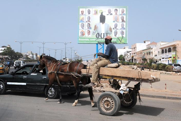 """A man on a horse-drawn cart rides past a campaign poster for incumbent Dakar Mayor Khalifa Sall (C) with the """"Out"""" written on it, in a street of Dakar, Senegal, on June 26, 2014 (AFP Photo/Seyllou)"""