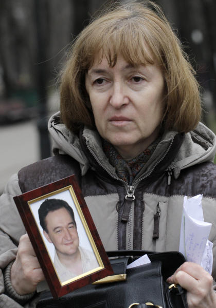 FILE - In this Nov. 30, 2009 file photo, Nataliya Magnitskaya, mother of lawyer Sergei Magnitsky who died in jail, holds a photo of her son as she speaks during an interview with the Associated Press in Moscow, Russia. Russian prosecutors have announced a new criminal case against Kremlin critic Bill Browder and say he might be behind the death of his former employee, Sergei Magnitsky, in a Russian prison. (AP Photo/Alexander Zemlianichenko, File)