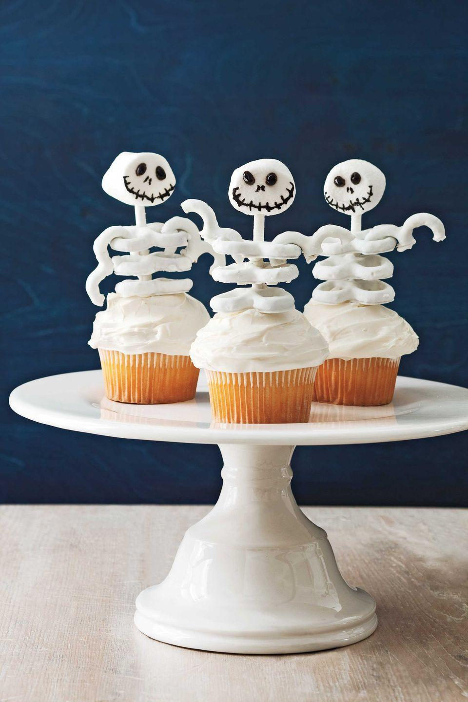 """<p>Who could resist a cute cupcake with a skeletal frame comprised of a marshmallow skull and yogurt mini pretzel ribs? Whip up a batch of these bony characters with your favorite cake mix and canned frosting.</p><p><a href=""""https://www.womansday.com/food-recipes/food-drinks/recipes/a11450/skeleton-cupcakes-recipe-122708/"""" rel=""""nofollow noopener"""" target=""""_blank"""" data-ylk=""""slk:Get the Skeleton Frame Cupcakes recipe."""" class=""""link rapid-noclick-resp""""><em>Get the Skeleton Frame Cupcakes recipe.</em></a></p>"""