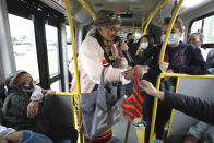 """Marlene Alfonso, a 69-year-old Venezuelan grandmother who goes by """"Toothless Cindy,"""" accepts coins from commuters as she sings about Venezuelan migrants' lives in hopes of tips from commuters on the Transmilenio, the crowded and crime-ridden public bus system in Bogota, Colombia, Tuesday, Nov. 3, 2020. Alfonso, who is missing most of her teeth and can't afford false ones, says she can make about $8 a day from tips, enough to pay rent and send some money home to her daughter. (AP Photo/Fernando Vergara)"""