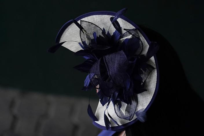 A woman wearing a white hat with blue feathers and ribbon on it.