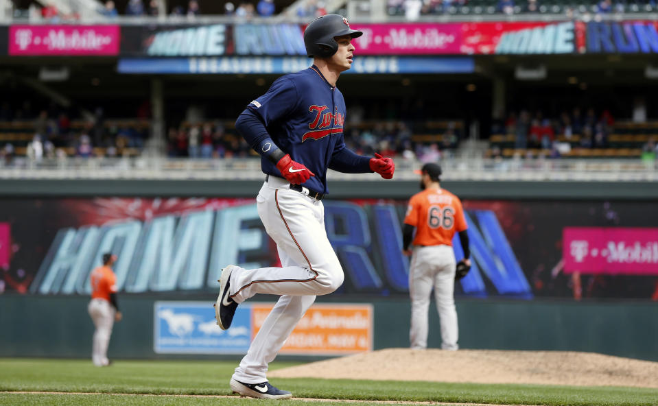 Minnesota Twins' Max Kepler, foreground, jogs home on his two-run home run off Baltimore Orioles relief pitcher Tanner Scott, back right, in the sixth inning of a baseball game Saturday, April 27, 2019, in Minneapolis. (AP Photo/Jim Mone)