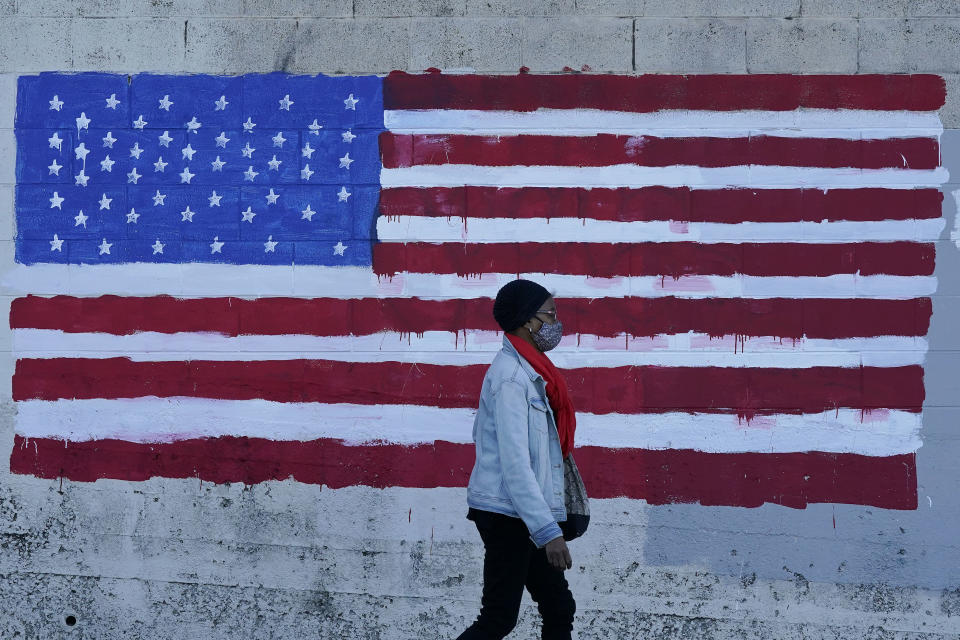 FILE - In this Nov. 16, 2020, file photo, a woman wears a mask while walking past an American flag painted on a wall during the coronavirus outbreak in San Francisco. A deadly rise in COVID-19 infections is forcing state and local officials to adjust their blueprints for fighting a virus that is threatening to overwhelm health care systems. (AP Photo/Jeff Chiu, File)