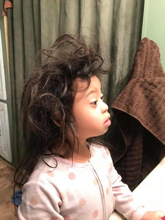 Young girl with Down syndrome looking at knotted hair in the mirror