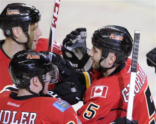 Calgary Flames' Mark Giordano, right, celebrates his overtime goal against the Phoenix Coyotes with Steve Begin, top left, and Jiri Hudler, from Czech Republic, during third period of an NHL hockey game in Calgary, Alberta, Friday April 12, 2013. (AP Photo/The Canadian Press, Larry MacDougal)