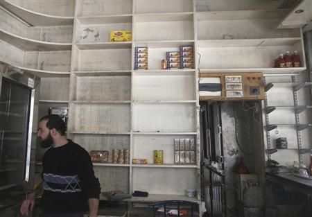 A man is seen inside a half-empty shop due to lack of supplies in the Duma neighbourhood of Damascus
