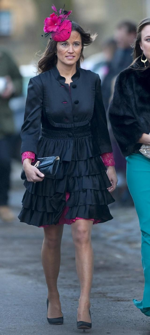 <p>For the wedding of Katie Percy and Patrick Valenine, held at St. Michael's Church in Alnwick in February 2011, Pippa wore a black and fuchsia ensemble. <em>(Photo: PA)</em> </p>